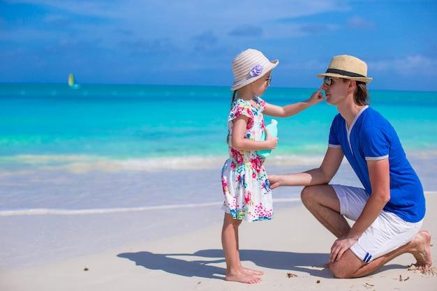 Petite fille frotte l'écran solaire sur le nez de son père