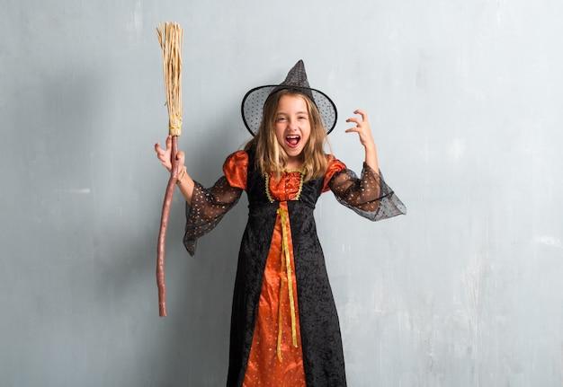 Petite fille frustrée habillée en sorcière et tenant un balai pour les fêtes d'halloween