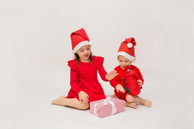 Une petite fille et un garçon en bonnets rouges ouvrent un cadeau du nouvel an sur un mur blanc avec un espace pour le texte