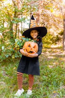 Petite fille et garçon découpant la citrouille à l'halloween. des enfants déguisés trompent ou traitent. des bonbons ou un sort pour les enfants. enfant en costume de sorcière jouant dans le parc en automne. enfant en bas âge avec jack-o-lanterne.