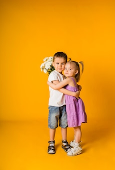 Une petite fille et un garçon embrassent et tiennent un bouquet de fleurs sur une surface jaune avec un espace pour le texte