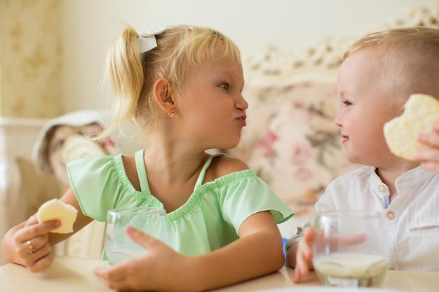 Petite fille et garçon faisant des visages au petit déjeuner