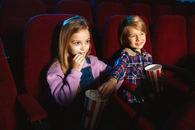Petite fille et garçon regardant un film dans un cinéma