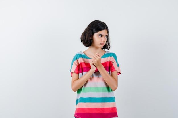 Petite fille gardant les mains jointes en t-shirt et regardant pensive, vue de face.