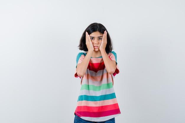 Petite fille gardant les mains sur les joues en t-shirt et ayant l'air impuissante, vue de face.