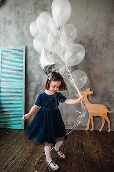 La petite fille garde des ballons dans la chambre