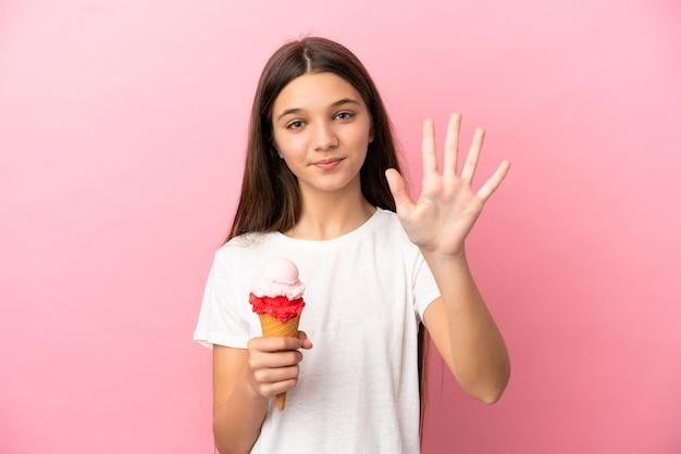 Petite fille avec une glace au cornet sur fond rose isolé comptant cinq avec les doigts