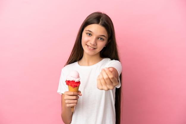 Petite fille avec une glace au cornet sur fond rose isolé faisant un geste d'argent