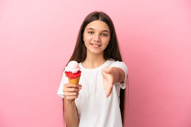 Petite fille avec une glace au cornet sur fond rose isolé se serrant la main pour conclure une bonne affaire