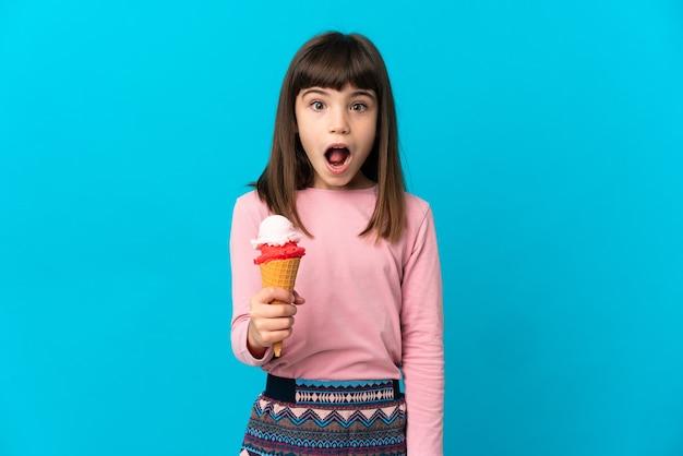 Petite fille avec une glace au cornet isolée sur fond bleu avec une expression faciale surprise