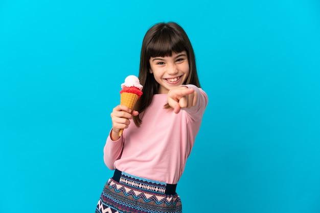 Petite fille avec une glace au cornet isolée sur fond bleu pointant vers l'avant avec une expression heureuse
