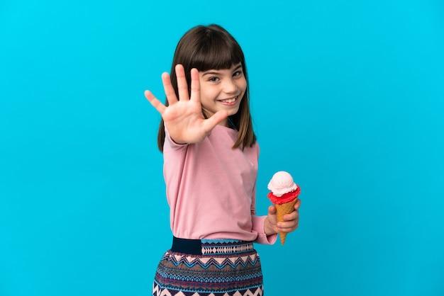 Petite fille avec une glace cornet isolée sur fond bleu en comptant cinq avec les doigts