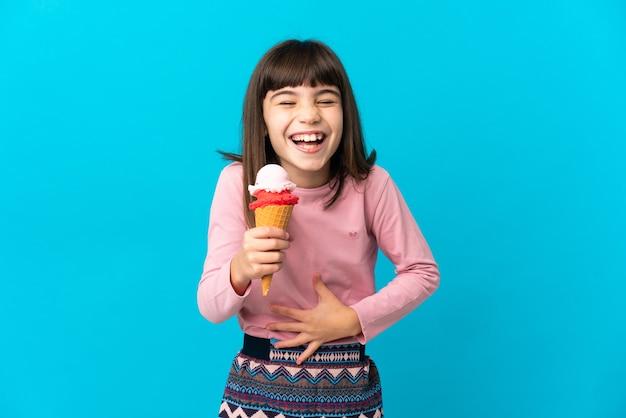 Petite fille avec une glace cornet isolée sur fond bleu souriant beaucoup