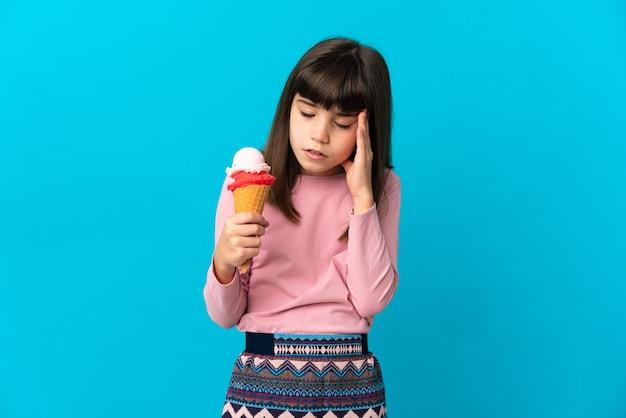 Petite fille avec une glace cornet isolée sur mur bleu avec maux de tête
