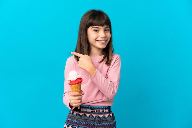 Petite fille avec une glace cornet isolée sur un mur bleu pointant vers le côté pour présenter un produit