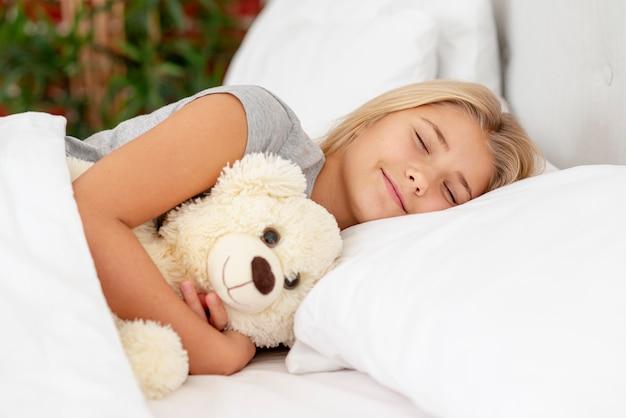 Petite fille glissant avec son ourson en jouet