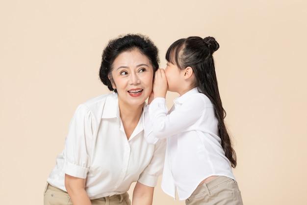 Petite fille et grand-mère chuchotant