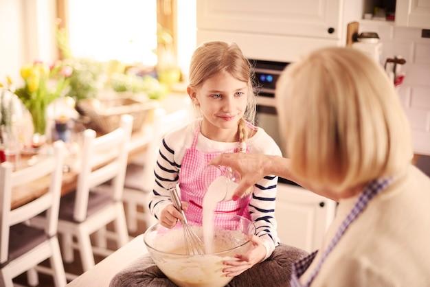 Petite-fille et grand-mère avec équipement de cuisson