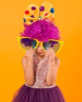 Petite fille avec de grandes lunettes de soleil et perruque de clown