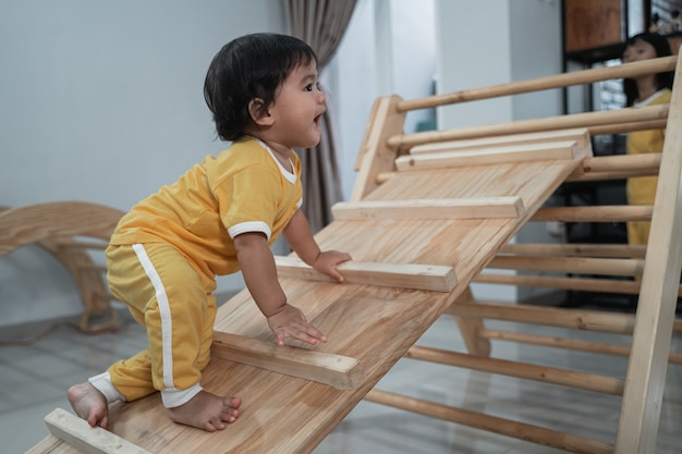 Petite fille grimpant dans des jouets triangle pikler dans le fond du salon