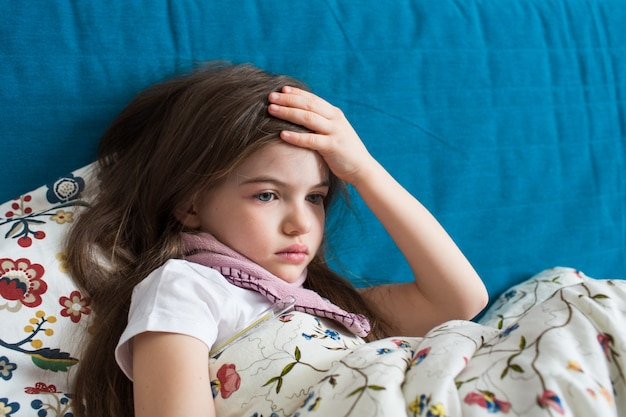 Une petite fille a la grippe, se trouve à la maison sous une couverture