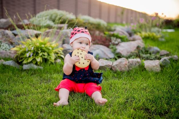 Petite fille avec un gros biscuit au chocolat sur la cour arrière