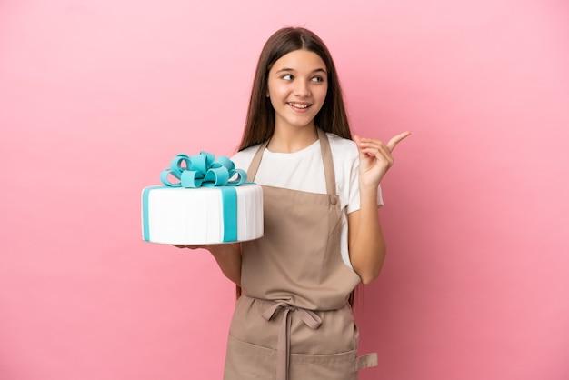 Petite fille avec un gros gâteau sur fond rose isolé ayant l'intention de réaliser la solution tout en levant un doigt vers le haut