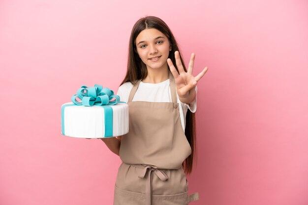 Petite fille avec un gros gâteau sur fond rose isolé heureux et comptant quatre avec les doigts