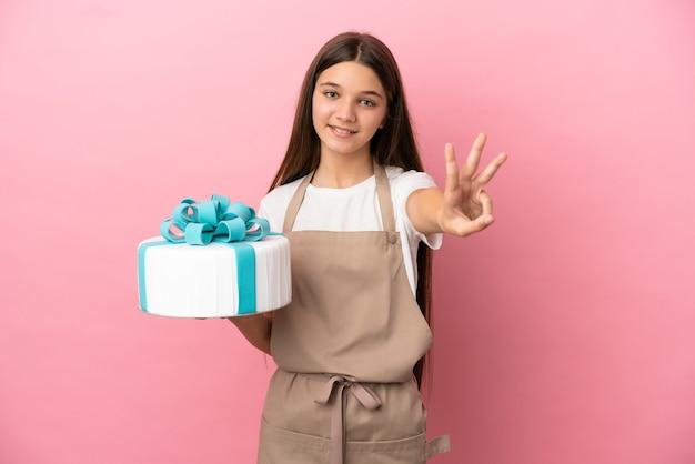 Petite fille avec un gros gâteau sur fond rose isolé heureux et comptant trois avec les doigts