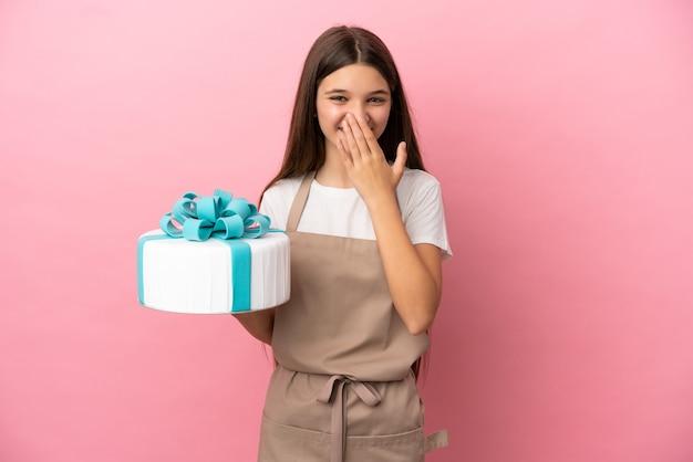 Petite fille avec un gros gâteau sur fond rose isolé heureux et souriant couvrant la bouche avec la main