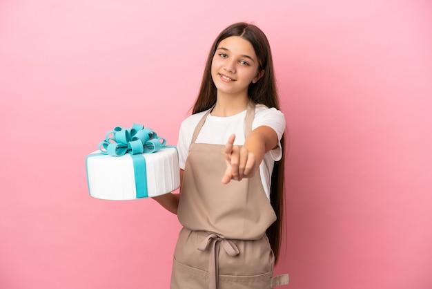 Petite fille avec un gros gâteau sur fond rose isolé montrant et levant un doigt