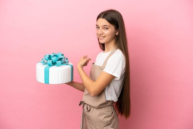 Petite Fille Avec Un Gros Gâteau Sur Fond Rose Isolé Pointant Vers L'arrière Photo Premium