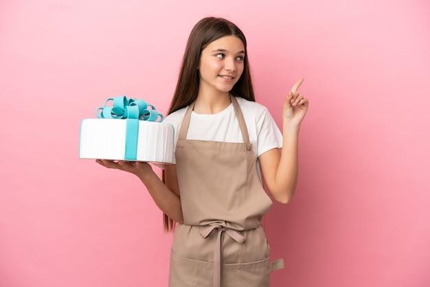 Petite fille avec un gros gâteau sur fond rose isolé pointant vers une excellente idée