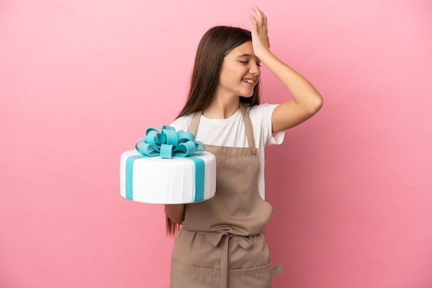 Petite fille avec un gros gâteau sur fond rose isolé a réalisé quelque chose et a l'intention de la solution