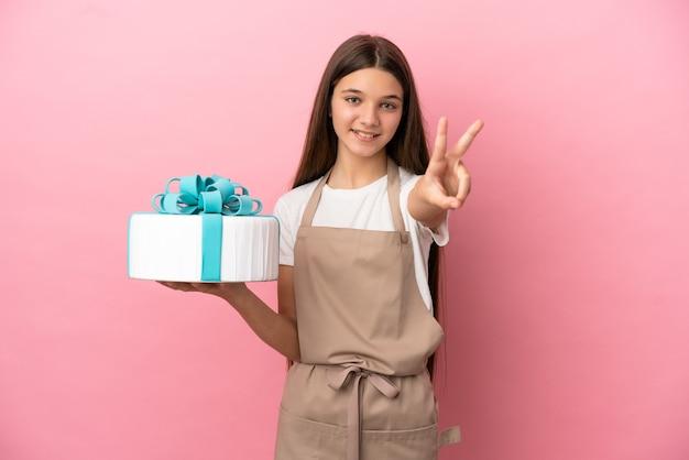 Petite fille avec un gros gâteau sur fond rose isolé souriant et montrant le signe de la victoire