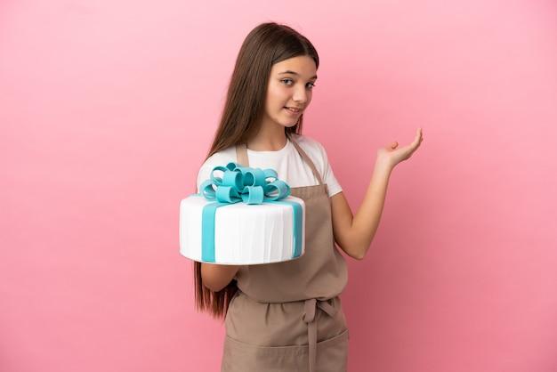 Petite fille avec un gros gâteau sur une surface rose isolée étendant les mains sur le côté pour inviter à venir
