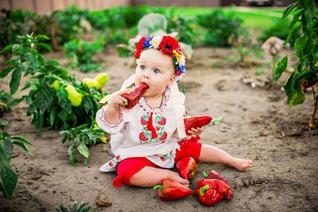 Petite fille avec un gros poivron rouge sur la cour arrière
