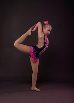Petite fille en gymnaste en costume debout en position en studio, faisant un cercle avec la jambe et le bras.