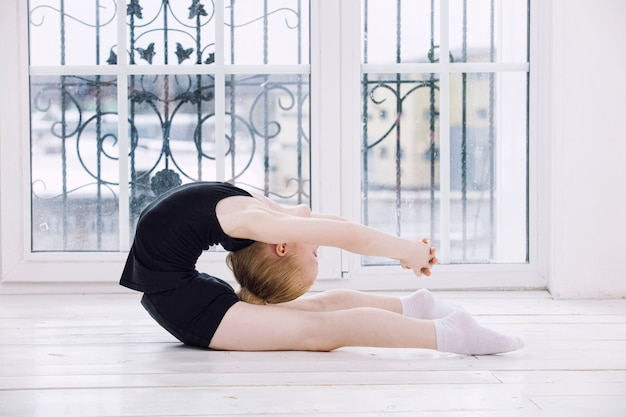 Petite fille gymnaste enfant faisant des étirements dans une pièce lumineuse sur un fond de fenêtre heureux et mignon