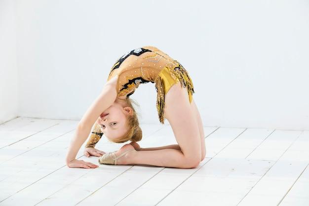 Petite fille gymnaste enfant faisant des étirements dans une pièce lumineuse sur un heureux et mignon