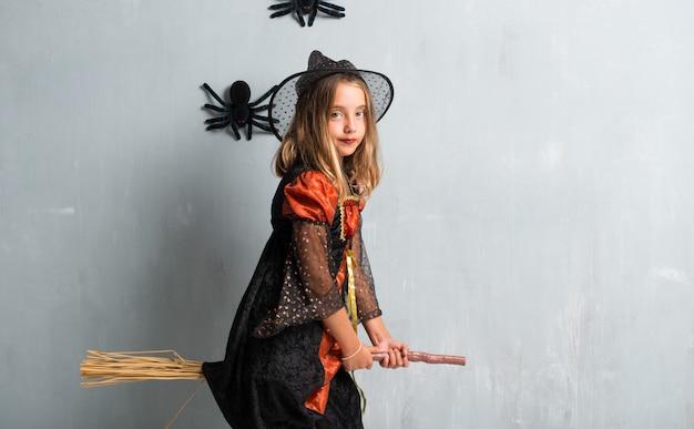 Petite fille habillée comme une sorcière pour les vacances d'halloween ci-dessus sur le balai et le vol