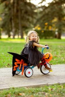 Petite fille habillée en costume de sorcière à vélo avec des citrouilles et des bonbons