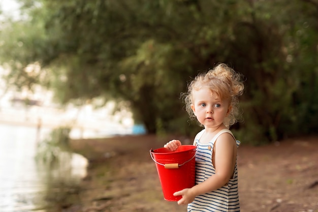 Petite fille habillée en marin sur une plage de sable avec des coquillages au bord de la mer