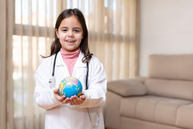 Petite fille habillée en médecin tenant une balle mondiale dans ses mains