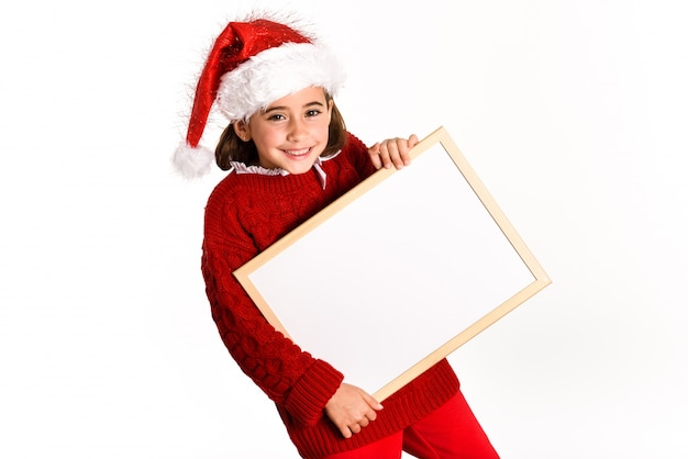 Petite fille habillée en père noël tenant un tableau blanc