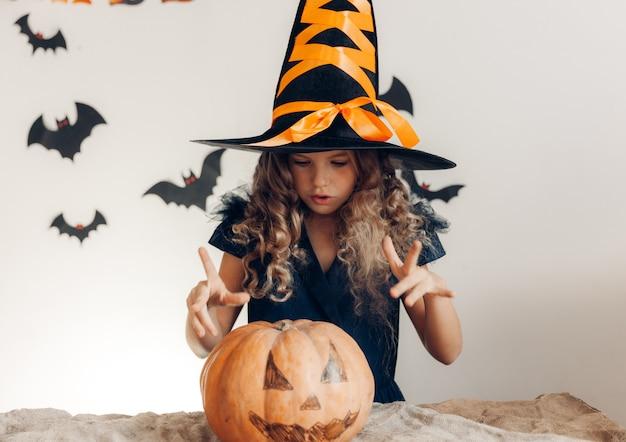 Petite fille habillée en sorcière avec une citrouille. halloween. citrouille pour halloween