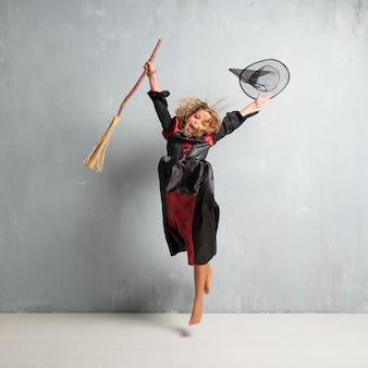Petite fille habillée en sorcière pour les vacances d'halloween sautant
