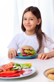 Petite fille avec un hamburger végétarien végétarien en bonne santé