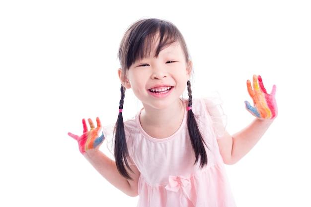 Petite fille heureuse asiatique montrant peint la main sur fond blanc