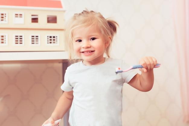 Petite fille heureuse avec une brosse à dents souriant et regardant la caméra